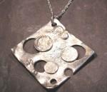 large silver holed pendant