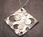 large silver holed pendant